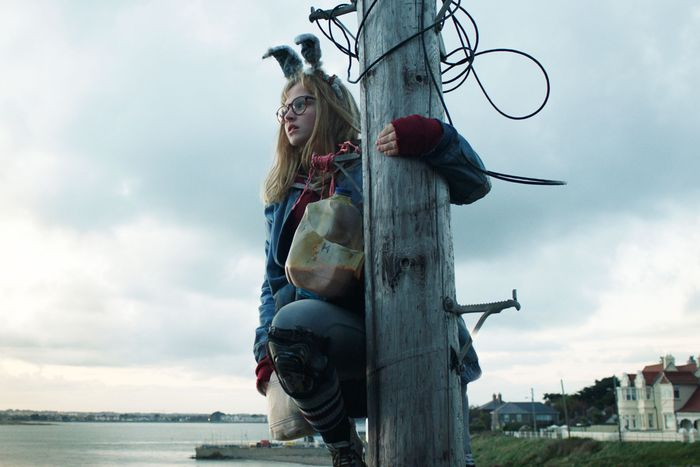 Barbara, with bunny ears on her head and a plastic jug with a mysterious liquid, looks into the distance from atop a telephone pole she has climbed.