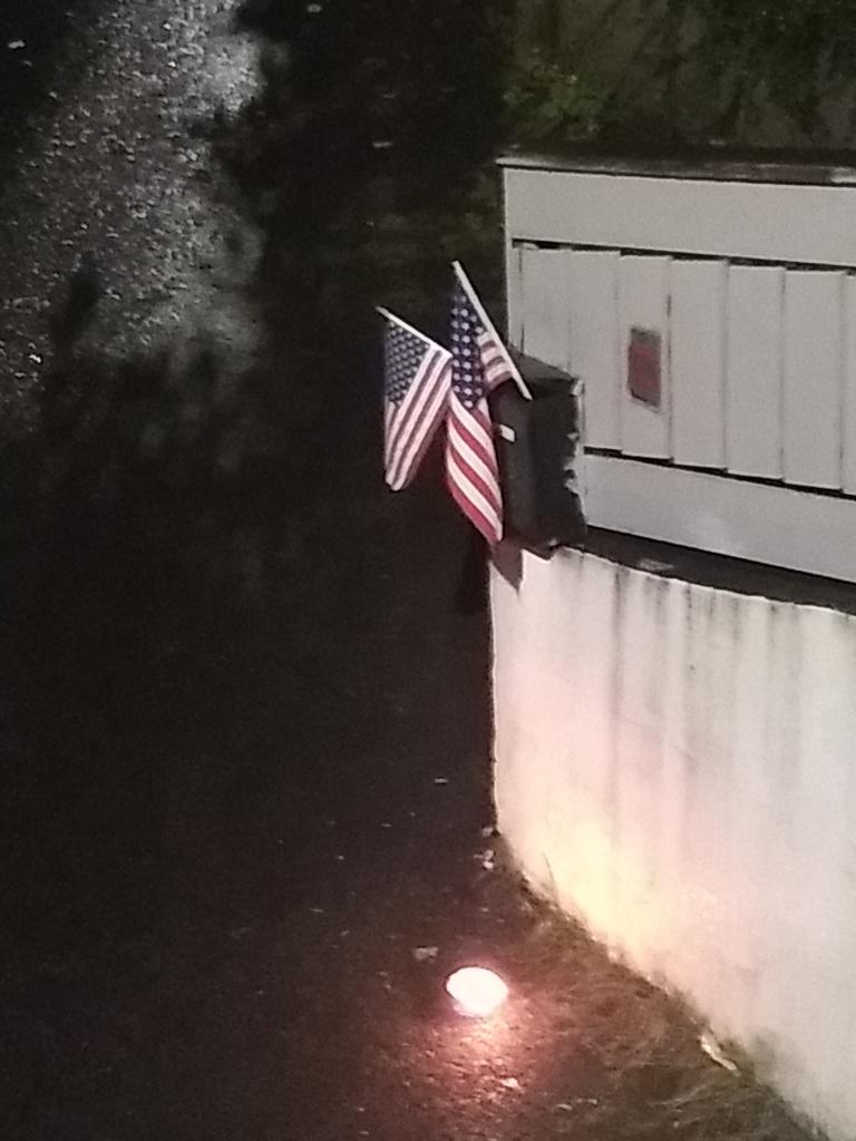 Amerikanske flagg og fakkel i mørket utenfor foreldrene mine sitt hus.