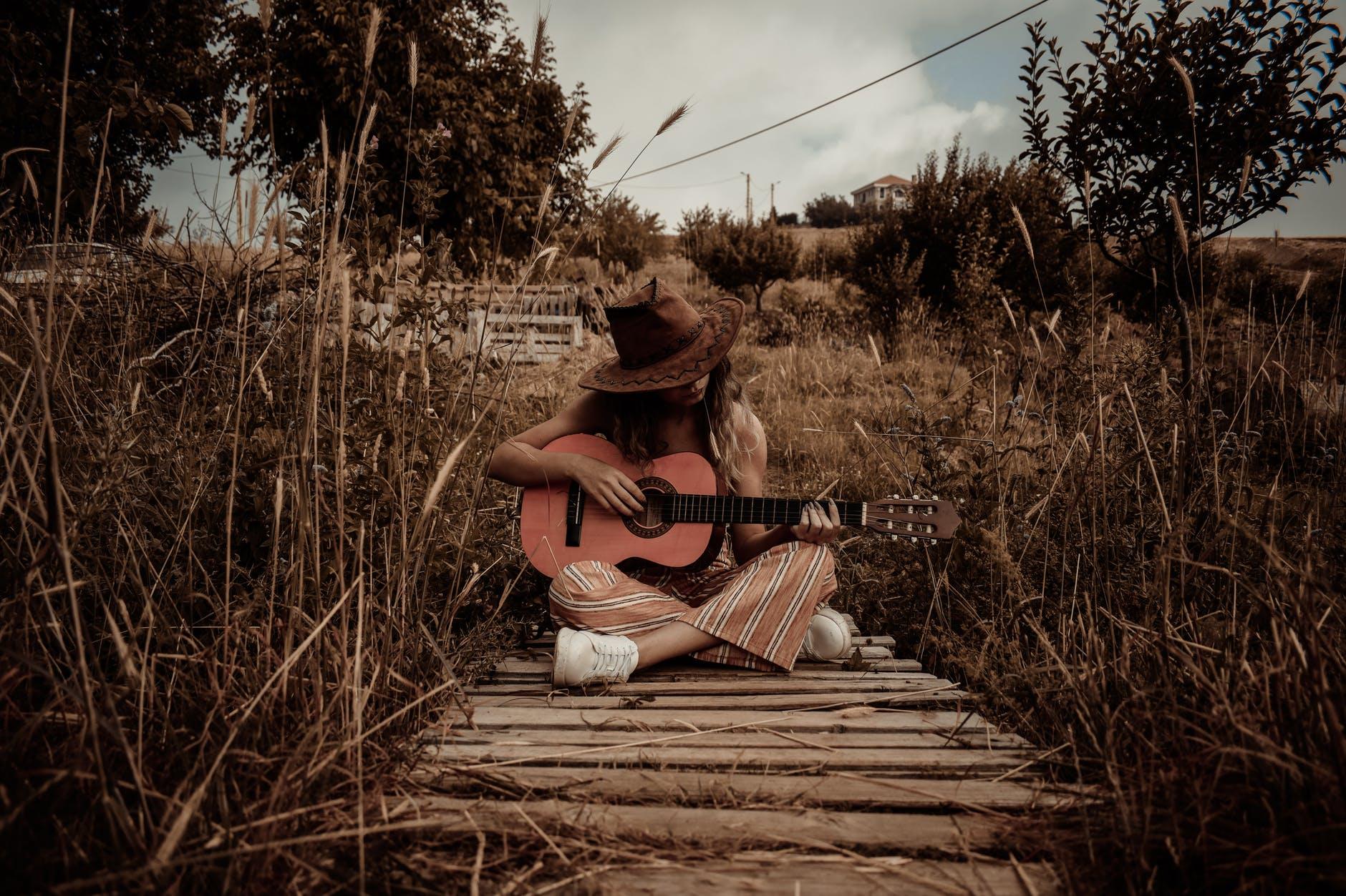 En jente med cowboyhatt og gitar sitter med beina i kors på en brygge i et sørstatslandskap.