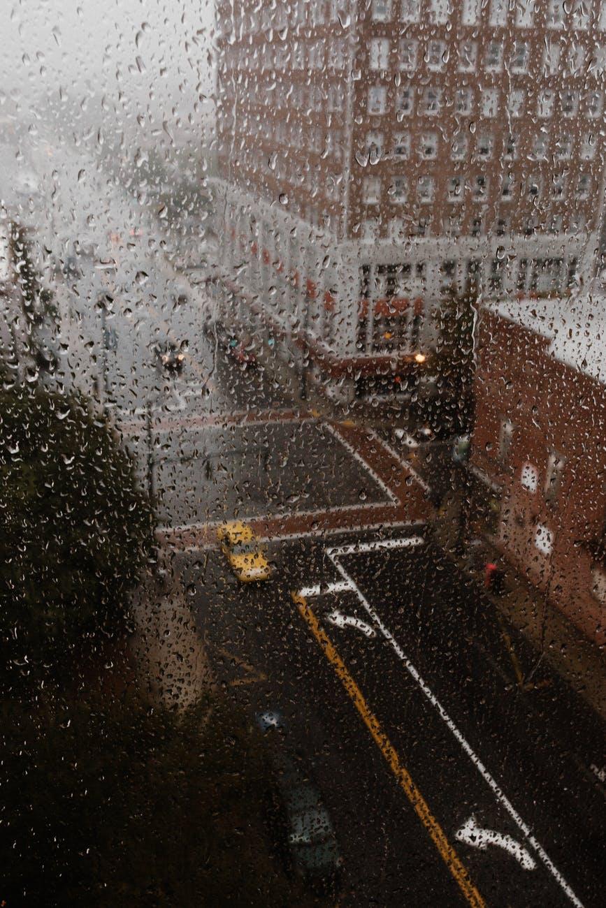 Illustrasjonsbilde av en regntung gate i en amerikansk storby, sett gjennom et vindu med mange regndråper.