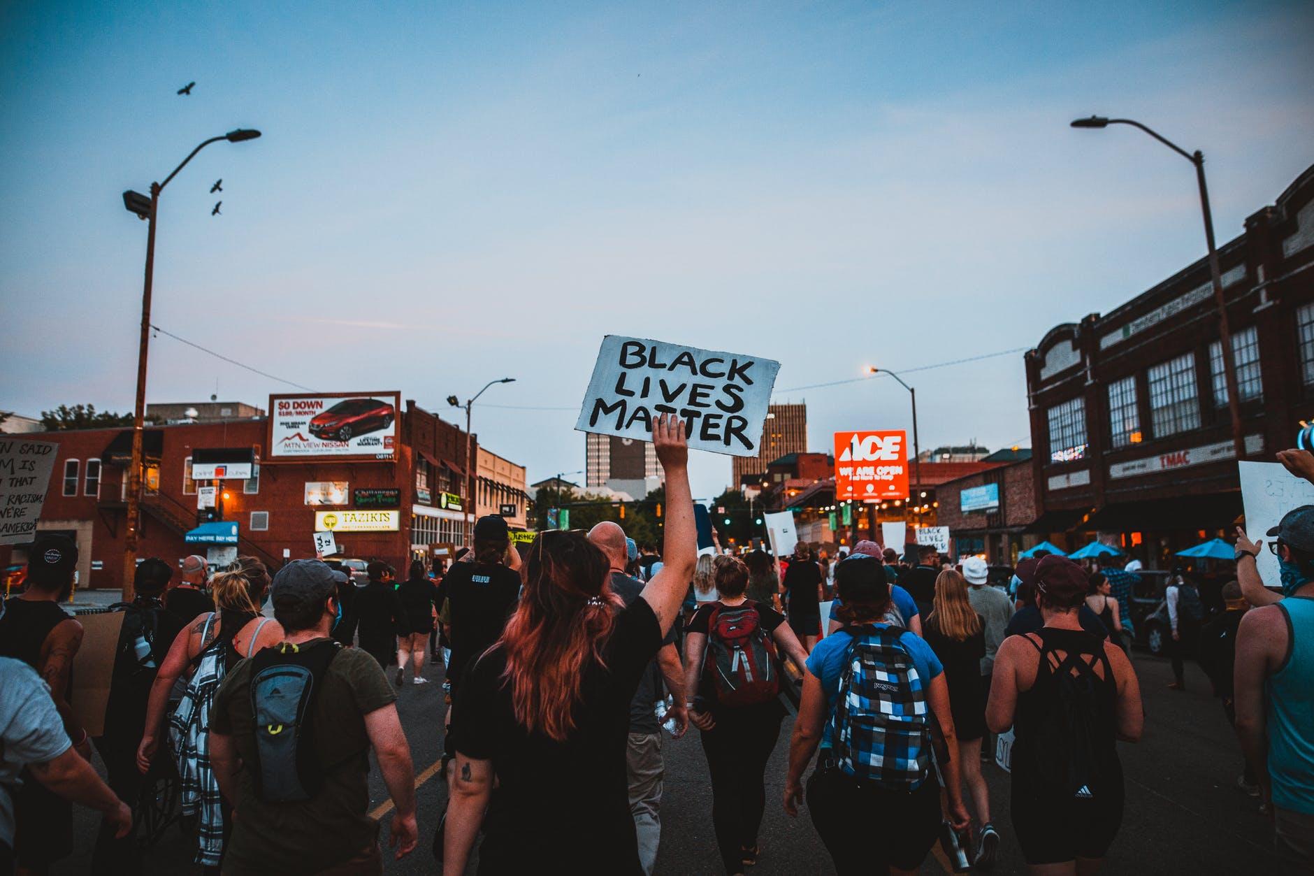 """Mennesker som går i tog mot  rasisme i USA. En av dem bærer en plakat med påskriften """"BLACK LIVES MATTER""""."""
