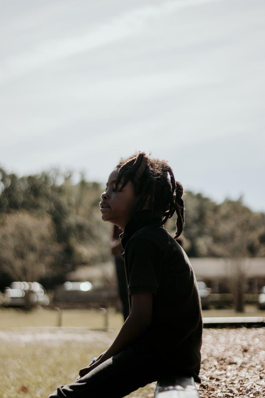 Sittende afro-amerikansk ungdom med rastafletter og svarte klær i profil.