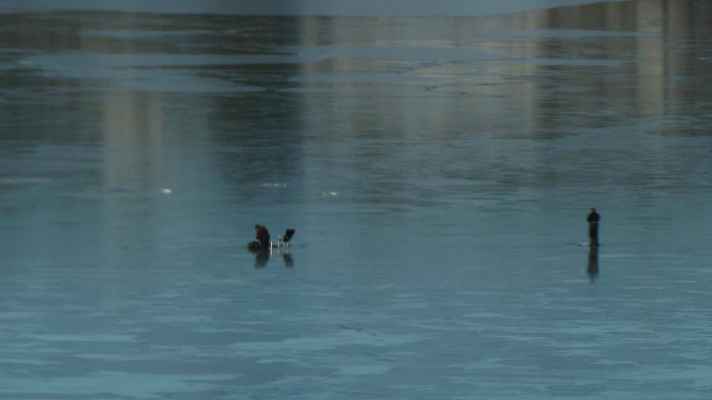 To isfiskere på isen, tatt med telelinse fra stuen min. Du ser den blå stålisen og én fisker til høyre i bildet som står oppreist ved en råk, og én i midten av bildet som sitter ved en sammenleggbar campingstol ved en annen råk.