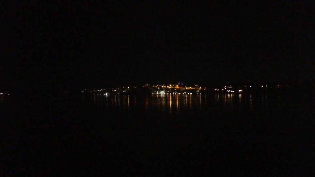 Utsikt mot lysene på land i mørket.