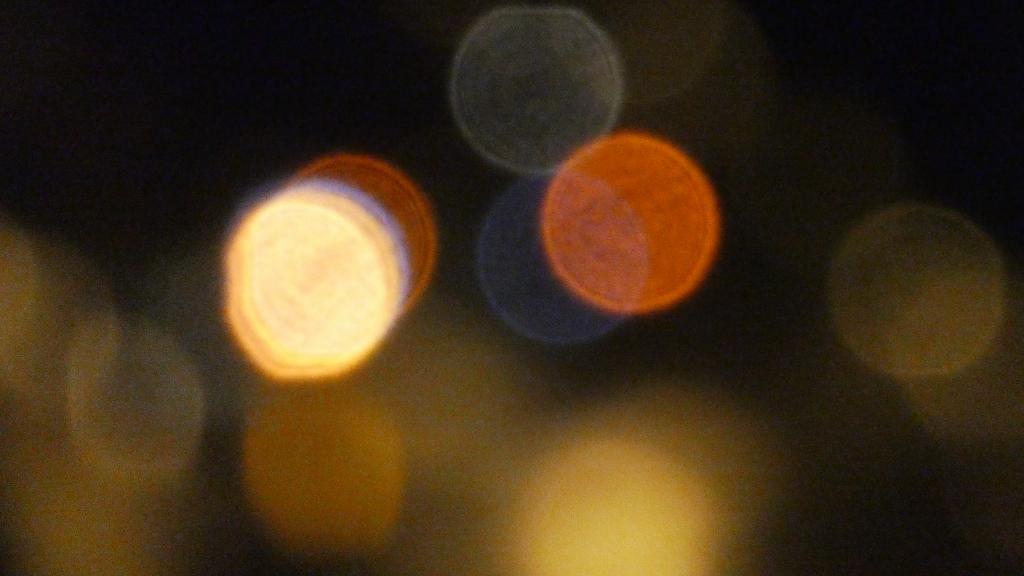 Uskarpt, stemningsfullt bilde av fargerike lys gjennom en vindusrute i mørket.