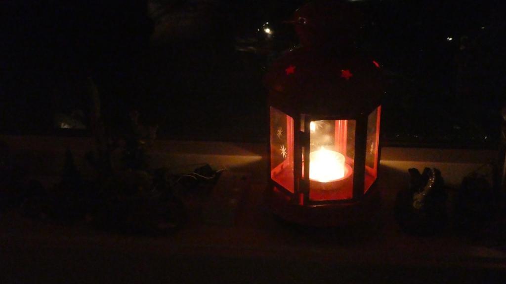 En rød lykt med telys i vinduskarmen i den mørke loftstuen.